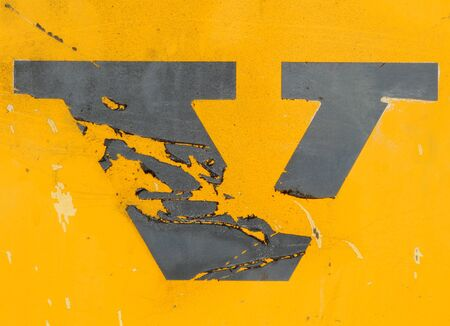 The letter V in peeling black paint on the side of an industrial machine  Stock Photo