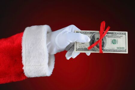 Santa Claus hand with cash tied up with a red ribbon. Horizontal format over a light to dark red background. Stock Photo