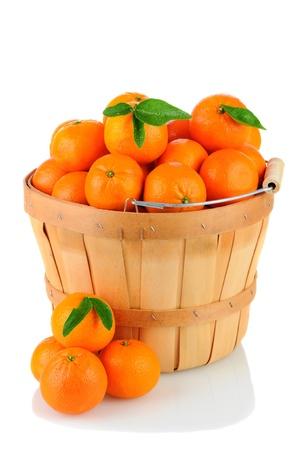 Een mand vol met Clementine mandarijn sinaasappelen. Verticale indeling op een witte achtergrond met reflectie.