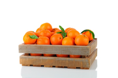 reticulata: A wood rustic crate full of Clementine Mandarin Oranges. Horizontal format over a white background with reflection.