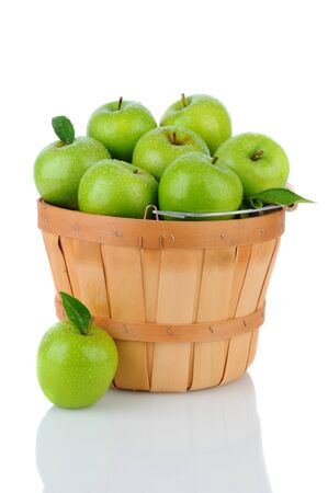 bushel: A basket full of fresh picked Granny Smith. Vertical format over a white background with reflection.