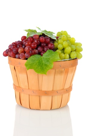 seedless: A wicker basket full of Red and Green Grapes. Vertical format on a white background with reflection.
