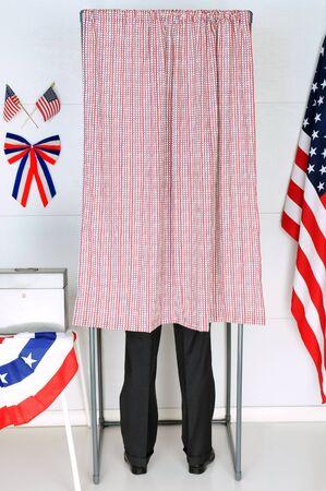 encuestando: Un hombre de pie en el interior de una cabina de votación en su lugar de votación local. Formato vertical, el hombre es irreconocible.