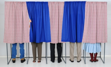 elections: A row of five voting booths with men and women casting their ballots at a polling place. Horizontal format, only showing the legs of the voters, people are unrecognizable..