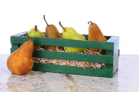 Bartlett and Bosc pears in a wooden crate on a granite counter top. Horizontal format with a white background. photo