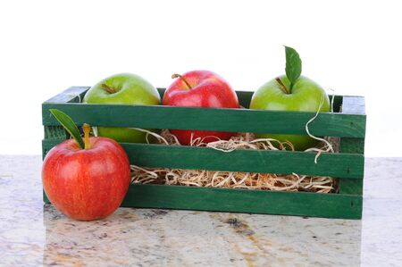 granny smith: Granny Smith and Gala Apples in a wooden crate on a granite counter top. Horizontal format with a white background. Stock Photo