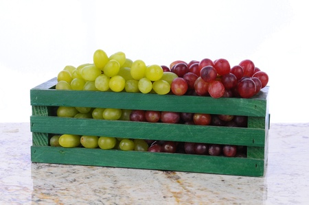 Red and green grapes in a wooden crate on a granite counter top. Horizontal format with a white background. Stock Photo - 15806803