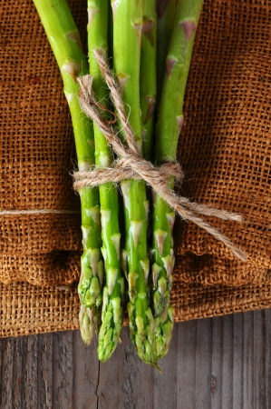 Closeup of Asparagus bunches tied with twine on a burlap and wood background photo