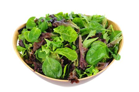 A Wooden bowl full of assorted salad greens, including, spinach, arugula, and romaine. Horizontal format on a white background.