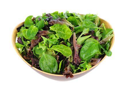 ensalada verde: Un cuenco de madera lleno de verduras para ensalada variadas, incluyendo, espinacas, rúcula y lechuga romana. Formato horizontal sobre un fondo blanco. Foto de archivo
