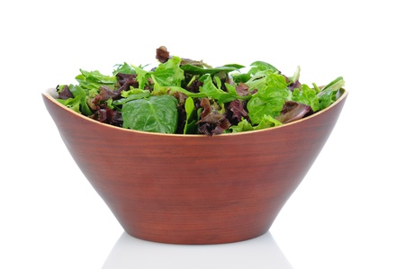 A Wooden bowl full of assorted salad greens, including, spinach, arugula, and romaine. Horizontal format on a white background. photo