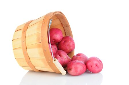A basket of red potatoes tipped over and spilling onto the reflective surface Stock Photo - 15868388