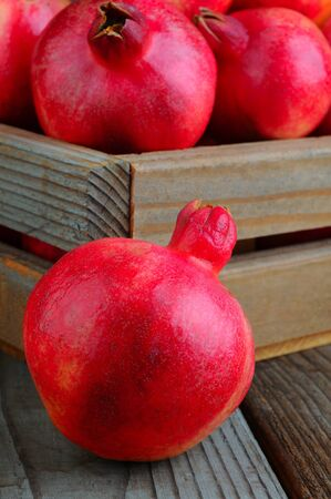 Closeup of a pomegranate on a wood surface in front of a crate full of fruit. Vertical Format. Stock Photo - 16010478