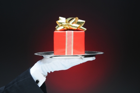 A butler wearing a tuxedo and white glove holding a tray with a wrapped present. Hand and arm only over a light to dark red background. Stock Photo