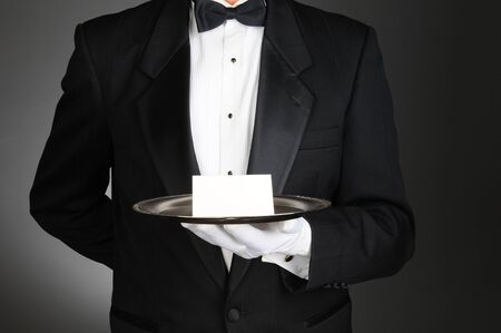 A butler wearing a tuxedo holding a note card on a silver tray in front of his torso. Man is unrecognizable over a light to dark gray background. photo