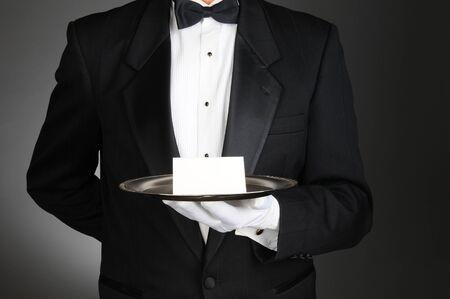 trays: Een butler het dragen van een smoking met een notitie kaart op een zilveren dienblad in de voorkant van zijn torso. De mens is onherkenbaar over een licht tot donker grijze achtergrond. Stockfoto