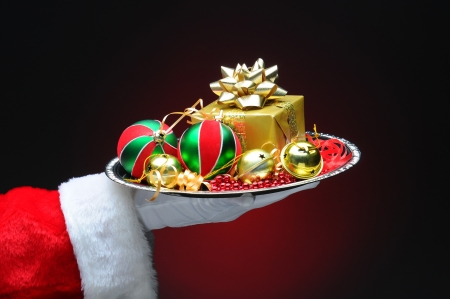Santa Claus hand holding a tray with decorations and a gift. Hand and arm only on a light to dark red background. Stock Photo - 16129139