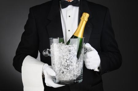 Close-up van een Sommelier met een Champagne Ijsemmer in de voorkant van zijn torso. Horizontale formaat op een licht naar donker grijze achtergrond. Stockfoto
