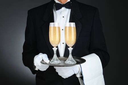 Closeup of a Sommelier holding two champagne glasses on a tray in front of his torso. Horizontal format on a light to dark gray background. Stock Photo