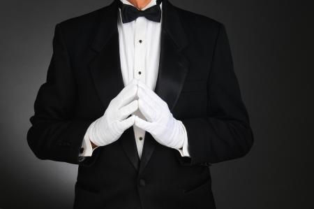 그의 몸통의 맨 앞에 함께 자신의 손으로 턱시도를 입고 남자의 근접 촬영 어두운 회색 배경에 빛을 인식 할 수없는 가로 형식입니다 스톡 콘텐츠