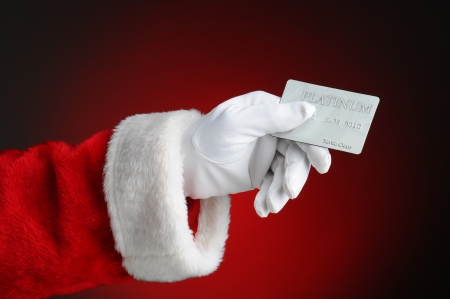 Closeup of Santa Claus hand holding a Platinum Credit Card  Horizontal format over a light to dark red background