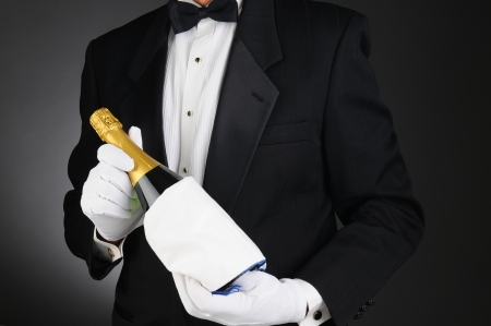 Closeup of a Sommelier holding a Champagne bottle in front of his torso  Man is unrecognizable  Horizontal format on a light to dark gray background