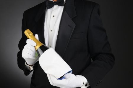 gastfreundschaft: Closeup of a Sommelier h�lt eine Flasche Champagner vor seinem Oberk�rper Man ist nicht wiederzuerkennen Querformat auf einem hell-bis dunkelgrau Hintergrund Lizenzfreie Bilder