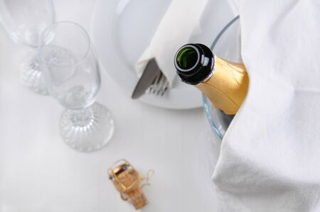 An open champagne bottle in an ice bucket on a table set for dinner