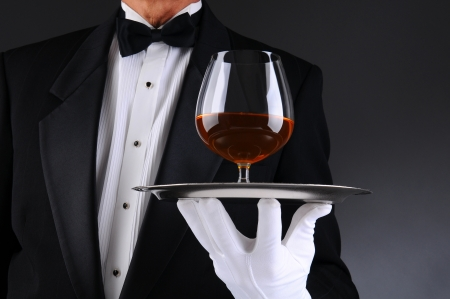 concierge: Closeup of a waiter wearing a tuxedo and holding a tray with a brandy snifter. Low angle man is unrecognizable. Horizontal format with a light to dark gray background.