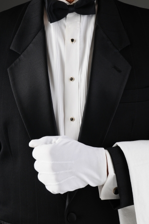 Closeup of a waiter wearing a tuxedo and white gloves. Man is unrecognizable and holding his lapel.