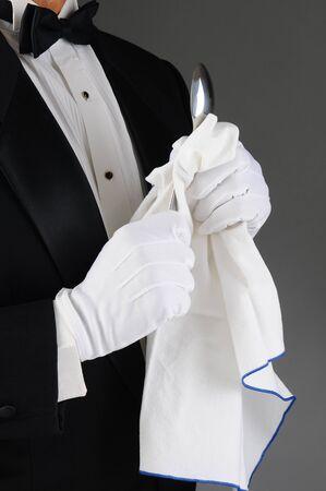 cubiertos de plata: Primer plano de un camarero que llevaba un esmoquin pulir una cuchara. Formato vertical sobre una luz de fondo gris oscuro. El hombre es irreconocible. Foto de archivo