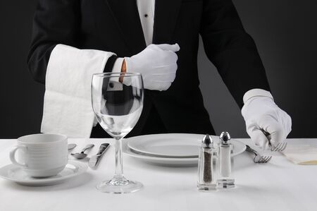 formal place setting: Closeup of a waiter in a tuxedo setting a formal dinner table. Shallow depth of field in horizontal format on a light to dark gray background. Man is unrecognizable. Stock Photo