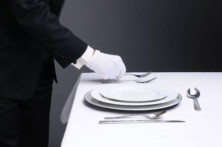 service desk: Closeup of a waiter in a tuxedo setting a formal dinner table. Horizontal format on a light to dark gray background. Man is unrecognizable. Stock Photo
