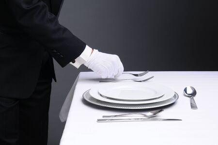 Primer plano de un camarero con un esmoquin establecer una mesa formal. Formato horizontal sobre una luz de fondo gris oscuro. El hombre es irreconocible.