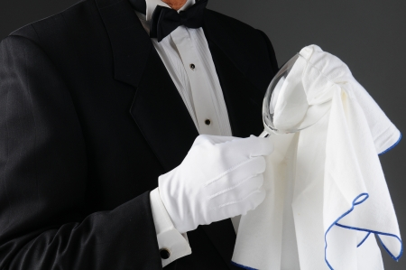Closeup of a waiter wearing a tuxedo polishing a wineglass. Horizontal format on a light to dark gray background. Man is unrecognizable.