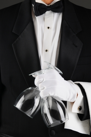 alcohol server: Closeup of a waiter in a tuxedo holding two wineglasses in front of his body. Man is unrecognizable.