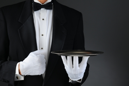 serving tray: Closeup of a tuxedo wearing waiter holding a silver tray in front of his body. Horizontal format on a light to dark gray background. Stock Photo