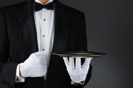 meseros: Primer plano de un camarero llevaba esmoquin sosteniendo una bandeja de plata en la parte delantera de su cuerpo. Formato horizontal sobre una luz de fondo gris oscuro.