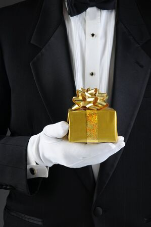 concierge: Closeup of a man wearing a tuxedo holding a Chrismas present in front of his body. Vertical format. Man is unrecognizable. Stock Photo