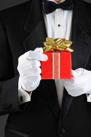 Closeup of a man wearing a tuxedo holding a chrismas present in front of his body. Vertical format, Man is unrecognizable.