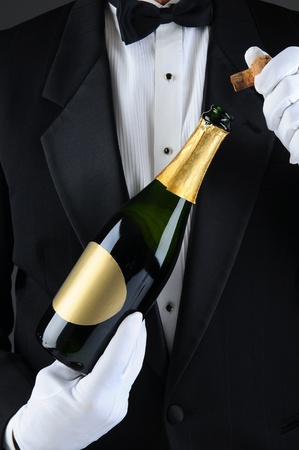 Closeup of a Sommelier uncorking a champagne bottle. Man is unrecognizable wearing a tuxedo and white gloves. Vertical Format. Imagens
