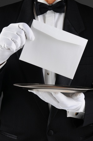 Closeup of a butler wearing a tuxedo holding a silver tray and an envelope. Vertical format, man is unrecognizable.