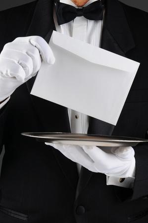 sobres para carta: Primer plano de un mayordomo que llevaba un esmoquin sosteniendo una bandeja de plata y un sobre. Formato vertical, el hombre es irreconocible.