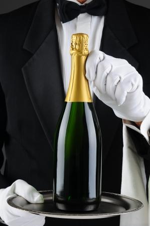 bouteille champagne: Gros plan d'un sommelier tenant une bouteille de champagne sur un plateau de service en face de son torse. Wan est v�tu d'un smoking et est m�connaissable. Format vertical.