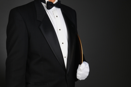 Closeup of a waiter in a tuxedo holding a serving tray under his arm. Horizontal format on a light to dark gray background. Man is unrecognizable. 스톡 콘텐츠