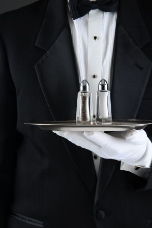 Closeup of a Waiter wearing a tuxedo holding a serving tray with salt and pepper shakers photo