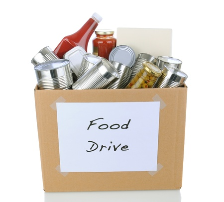 A box full of canned and packaged foodstuff for a charity food donation drive. Isolated on white with reflection. photo