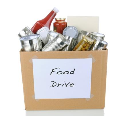 aandrijvingen: Een doos vol met blik en verpakte levensmiddel voor een goed doel voedsel donatie rijden. Geà ¯ soleerd op wit met reflectie.