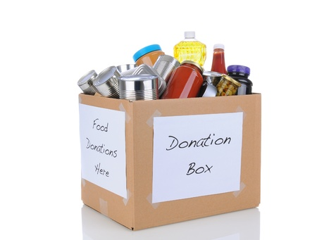 donations: A box full of canned and packaged foodstuff for a charity food donation drive  Isolated on white with reflection