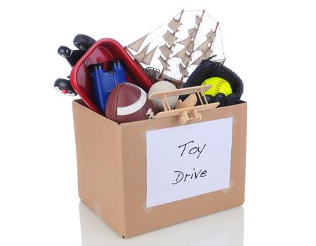 juguetes: Una caja llena de juguetes y material deportivo para una unidad de la caridad de fiesta. Aislado en blanco con la reflexi�n.